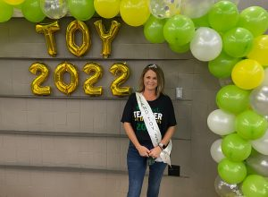 An image of Dana Williams standing in front of the teacher of the year balloons